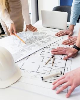 Nahaufnahme des architekten arbeitend an architekturplan auf tabelle