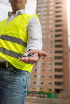 Nahaufnahme des architekten auf der baustelle, der schlüssel vom neuen zuhause hält holding