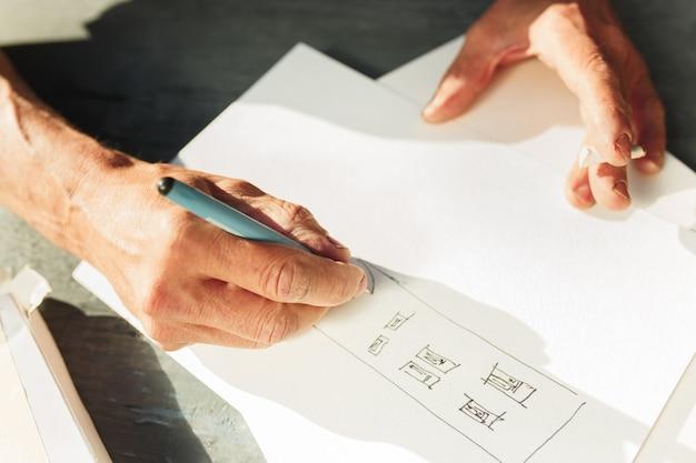 Nahaufnahme des architekten, der ein bauprojekt auf seinem flugzeugprojekt skizziert