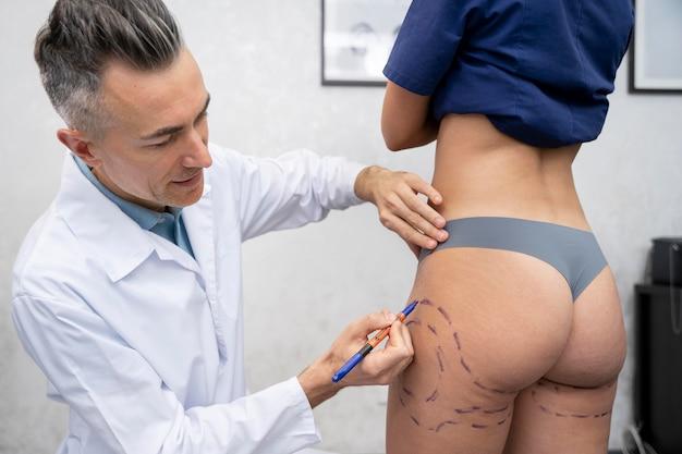 Nahaufnahme des arztes, der auf den körper des patienten zeichnet