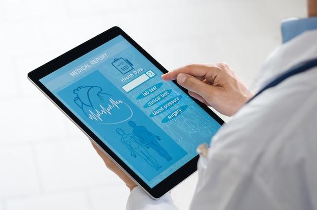 Nahaufnahme des arztes, der patientendaten auf digitalem tablett prüft