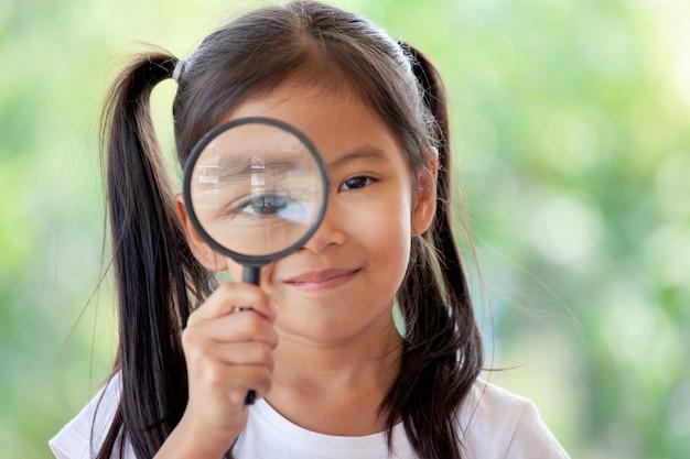 Nahaufnahme des asiatischen kindermädchens, das durch eine lupe schaut