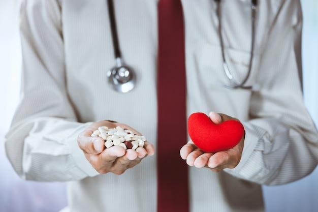 Nahaufnahme des asiatischen männlichen doktors, der pille und rotes herz im büro hält und zeigt
