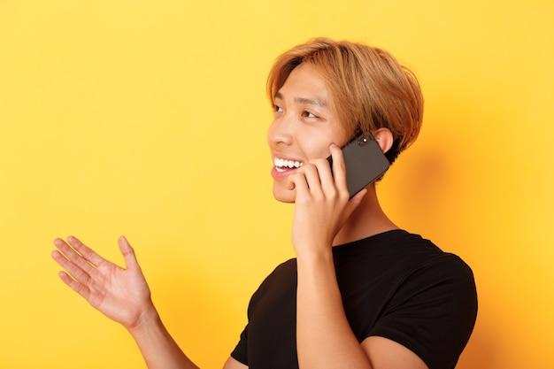 Nahaufnahme des attraktiven koreanischen kerls, der glücklich lächelt und auf handy spricht, links abbiegend, stehende gelbe wand.