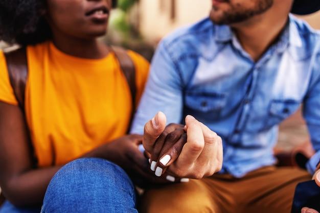 Nahaufnahme des attraktiven multikulturellen paares händchenhalten und flirten beim sitzen im freien.