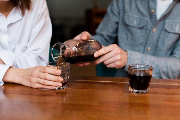 Nahaufnahme des auslaufenden kaffees des mannes in der schale für frau