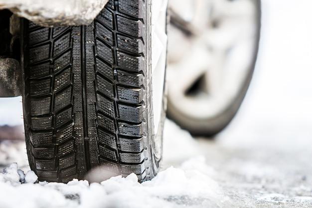 Nahaufnahme des autorades im winterreifen auf verschneiter straße