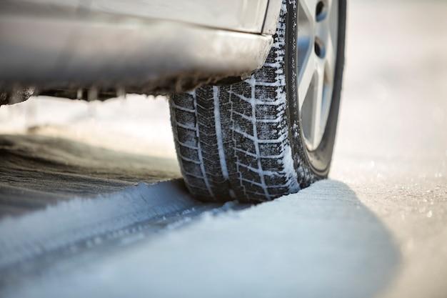 Nahaufnahme des autoradgummireifens im tiefen schnee. transport und sicherheit.