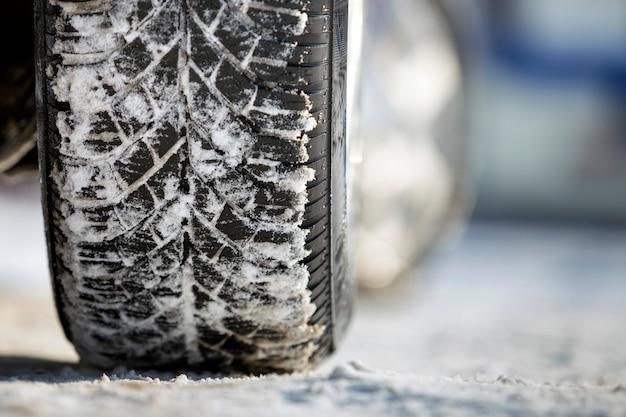 Nahaufnahme des autoradgummireifens im tiefen schnee. transport- und sicherheitskonzept.
