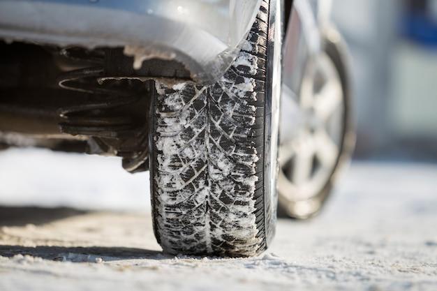 Nahaufnahme des autoradgummireifens im tiefen schnee.