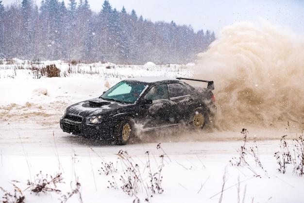 Nahaufnahme des autos, das im winter auf der mit schnee bedeckten straße treibt