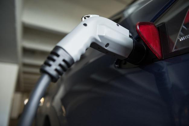 Nahaufnahme des autos, das mit elektroauto-ladegerät aufgeladen wird