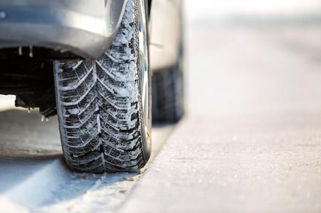 Nahaufnahme des autos drehen herein winterreifen auf schneebedeckter straße