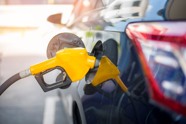 Nahaufnahme des autos füllt ölkraftstoff in der tankstelle nach