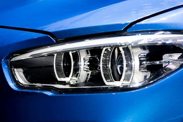 Nahaufnahme des autoscheinwerfers in der nacht. die vorderen lichter des blauen sportwagens. das licht des autos