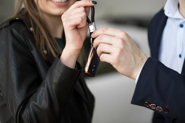 Nahaufnahme des autoverkäufers, der schlüssel zum neuen besitzer gibt