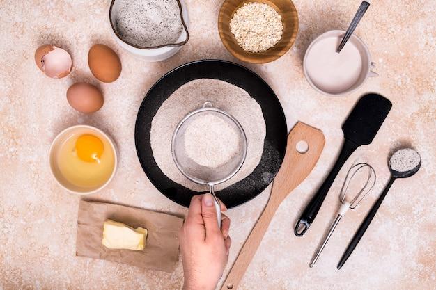 Nahaufnahme des bäckers mehl für den teig mit bestandteilen auf strukturiertem hintergrund siebend