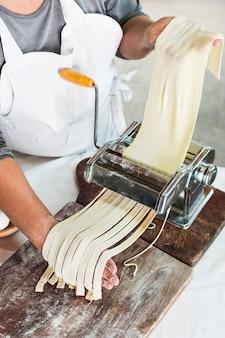 Nahaufnahme des bäckers rohen teig in bandnudeln auf teigwarenmaschine schneiden