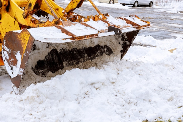Nahaufnahme des baggers für schneeräumung auf einem schneebedeckten parkplatz bedeckt nach blizzard