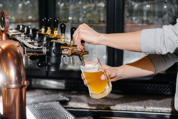 Nahaufnahme des barkeepers, der einen becher helles bier füllt