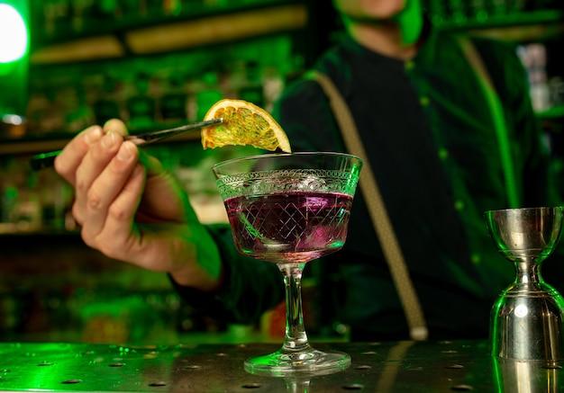 Nahaufnahme des barmanns beendet die zubereitung von alkoholischen cocktails in buntem neonlicht