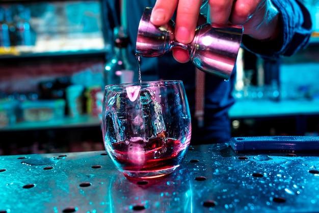 Nahaufnahme des barmanns beendet die zubereitung von alkoholischen cocktails und gießt getränke in neonlicht