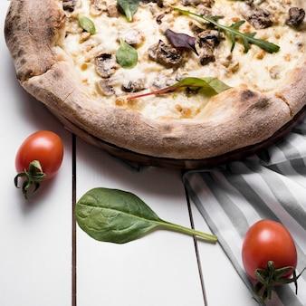 Nahaufnahme des basilikumblattes; kirschtomate und italienische pizza mit tischdecke auf holztisch