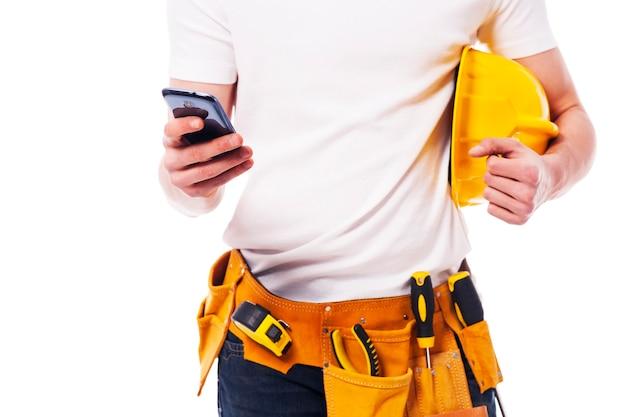 Nahaufnahme des bauarbeiters unter verwendung eines mobiltelefons
