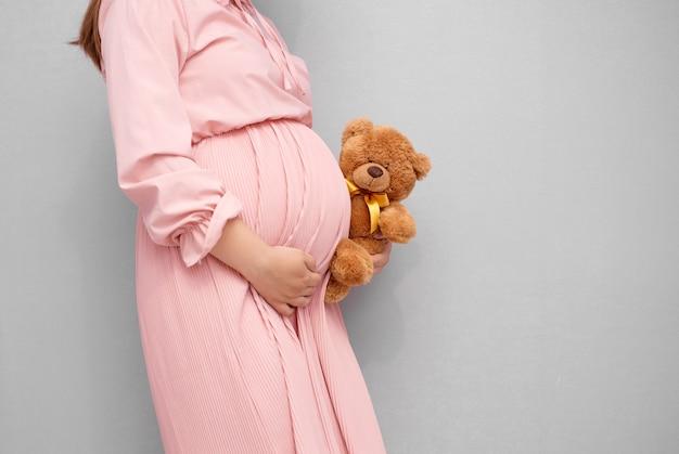 Nahaufnahme des bauches der schwangeren frau mit teddybärspielzeug.