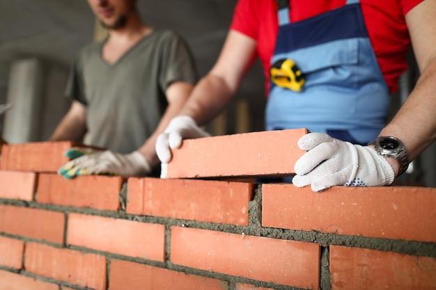 Nahaufnahme des bauherrn, der ziegelstein mit fachmann legt. arbeiter bei der arbeit, maurer, die mauer bauen, bauunternehmer und arbeiter.