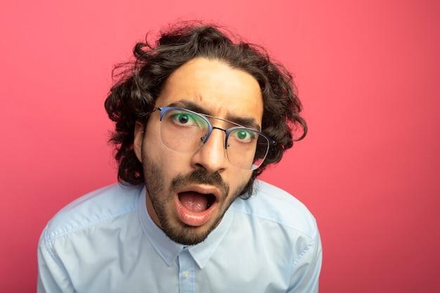Nahaufnahme des beeindruckten jungen gutaussehenden mannes, der brillen trägt, die front lokalisiert auf rosa wand betrachten