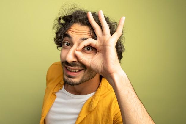 Nahaufnahme des beeindruckten jungen gutaussehenden mannes, der in der profilansicht steht, die blickgeste betrachtet, die front lokalisiert auf olivgrüner wand betrachtet