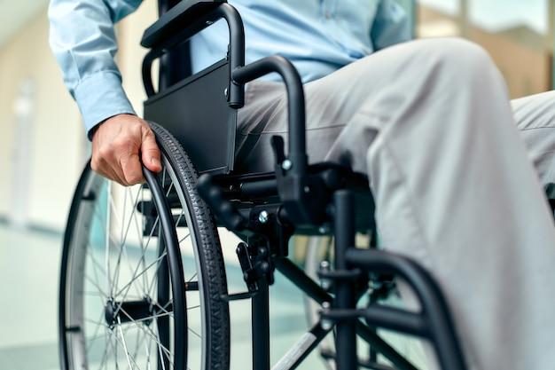 Nahaufnahme des behinderten älteren mannes, der im rollstuhl sitzt, der im krankenhaus betreut wird, behinderter reifer großvater im rollstuhl, älteres behinderungskonzept.