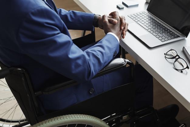 Nahaufnahme des behinderten geschäftsmannes im anzug, der im rollstuhl am tisch vor laptop im büro sitzt