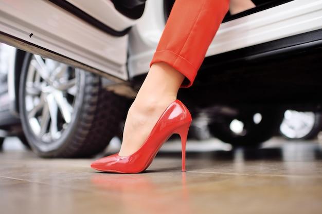 Nahaufnahme des beines einer frau in einem roten anzug und in roten schuhen gegen die oberfläche eines autos