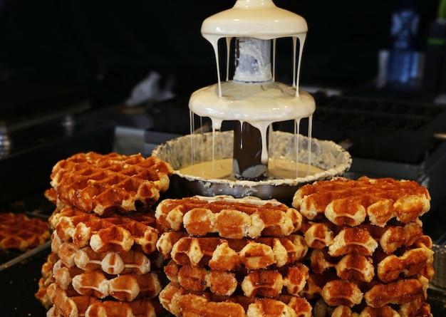 Nahaufnahme des belgischen flüssigen weißen schokoladenbrunnens für süße fondue-dip-desserts und traditionelle waffeln, niedrige winkelansicht
