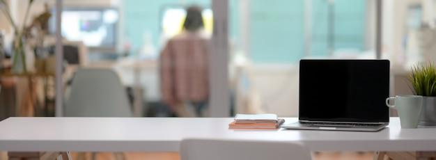 Nahaufnahme des bequemen schreibtischs mit offenem laptop, becher, baumtopf, notizbüchern und kopienraum
