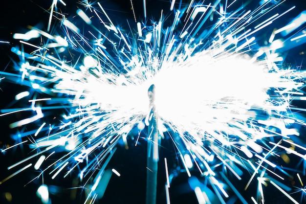 Nahaufnahme des blauen funkens eines brennenden feuers auf einem schwarzen hintergrund zu ehren des feiertags.