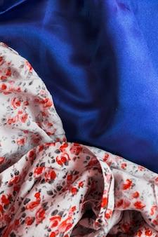 Nahaufnahme des blumenmustergewebes auf glattem blauem gewebe