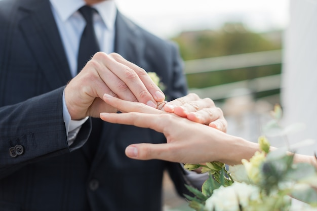 Nahaufnahme des bräutigams, der goldenen ring auf den finger der braut setzt