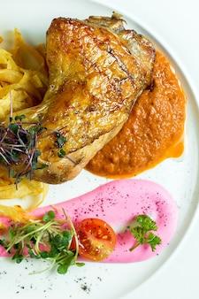 Nahaufnahme des brathähnchenbeins, das mit kartoffelchips und auberginenkaviar auf weißem teller serviert wird