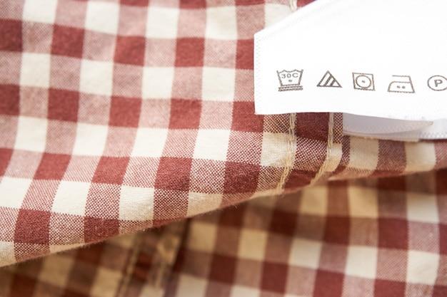 Nahaufnahme des braunen karierten hemdes des hellen kleidungsaufklebers. anleitung zur pflege des kleiderschranks