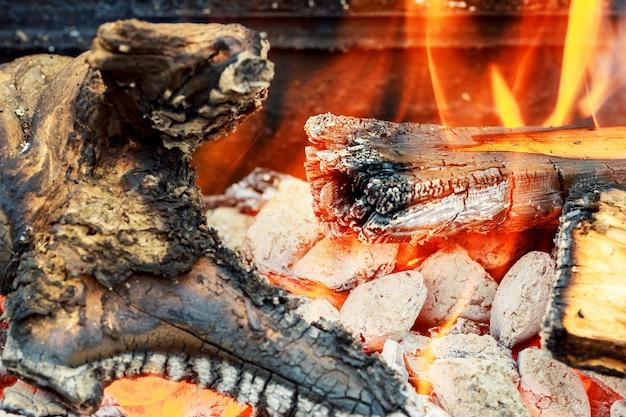 Nahaufnahme des brennholzes in den billets des feuers drei im heißen ofen brennend