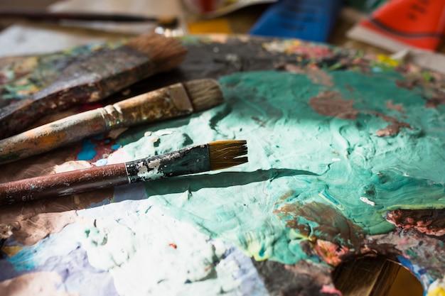 Nahaufnahme des bunten unordentlichen alten pinsels und der palette