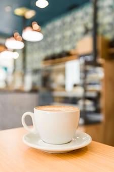 Nahaufnahme des cappuccinokaffees mit kunst latte auf holztisch