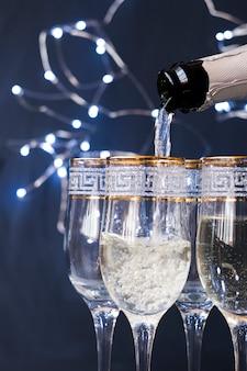 Nahaufnahme des champagners nachts gießend in das glas