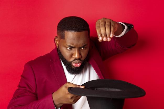 Nahaufnahme des charismatischen schwarzen männlichen magiers führen einen trick mit seinem hut durch