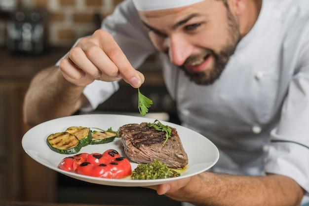 Nahaufnahme des chefs koriander auf gebratenem rindfleisch garnierend