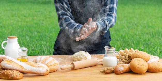 Nahaufnahme des chefs mit brot und frischer milch auf tabelle im garten. hausgemachte bäckerei.
