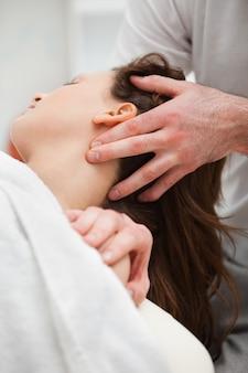 Nahaufnahme des chiropraktikers den hals seines patienten manipulierend